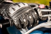 picture of motorcycle  - Human hand in a Motorcycle Racing Gloves holds a motorcycle throttle control - JPG