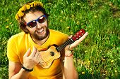stock photo of hippy  - Happy carefree young man sitting on a grass and playing his little guitar - JPG