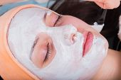 stock photo of rubber mask  - Spa therapy for young woman receiving facial mask at beauty salon - JPG