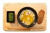 stock photo of condiment  - Chicken soup with noodles on a wooden plate served with sour green condiment and whole grain bread - JPG
