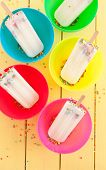 image of sprinkling  - Homemade frozen vanilla popsicles with colorful sprinkles - JPG