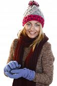 stock photo of imaginary  - Attractive woman wearing winter clothes smiling while forming imaginary snowball  - JPG