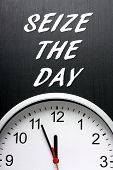 picture of midnight  - The phrase Seize The Day in white text on a blackboard next to a modern wall clock displaying the time at almost midnight - JPG