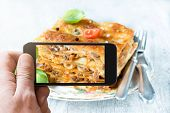 picture of lasagna  - Man photographing lasagna with mobile phone camera selective focus - JPG