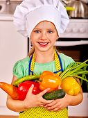 picture of pinafore  - Child in cooking hat holding vegetable at kitchen - JPG