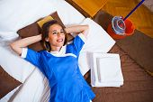 picture of maids  - Image of hotel maid lying in bed and day dreaming - JPG