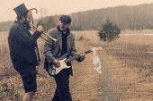 picture of gypsy  - Stylish gypsies play trumpet and electric guitar on a wilderness path - JPG