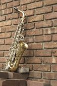 image of lonely  - Lone old saxophone leans against brick wall outside abandoned jazz club - JPG