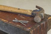 stock photo of work bench  - Old and worn contracting hammer and three nails on a distressed work bench - JPG