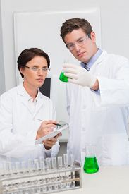 stock photo of beaker  - Scientists examining attentively beaker with green fluid in laboratory - JPG