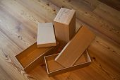 image of shoe-box  - three empty shoe boxes on a wooden floor - JPG