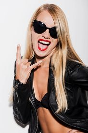 pic of cheeky  - Cheeky young woman in black bra and leather jacket looking at camera and gesturing while standing against white background - JPG