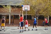 Basketball players practicing in basketball court outdoors poster
