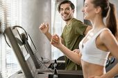 Determined young man smiling while running on treadmill during high-intensity interval training poster