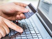 Online shopping using credit card and laptop. poster