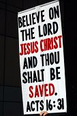 Poster urging people to believe in Jesus, held up during a demonstration