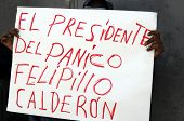 Protester in Mexico City holding hand-written sign blaming Mexican President Felipe Calderon for cau