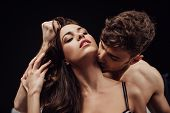 Man Passionately Kissing Beautiful Woman On Neck Isolated On Black poster
