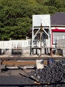image of bowser  - A steam train railway line with a water tank and a pile ot coal with a shovel and buckets - JPG