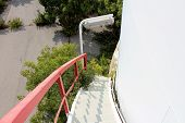 White Spiral Metal Stairs Mounted On Side Of Large Abandoned Storage Silo With Red Security Fence An poster