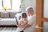 Grandmother Is Hugging Granddaughter In Cozy Home Living Room. Kind Senior Woman Is Telling Story Or poster