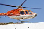 Orange And White Helicopter Landing At Heliport