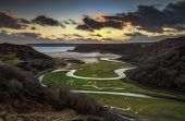 Sunset At Three Cliffs Bay Evening Sky Over The River At Three Cliffs Bay And The Great Tor At Penma poster