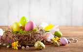 Easter composition with colorful Easter eggs in nest ,spring flowers and branches of pussy willows o poster
