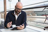 Focused Businessman Checking Daily Planner During Coffee Break. Young Bald Man In Casual And Eyewear poster