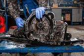 A Close-up Of A Young Man Repairman In A Working Uniform Of Cars Is Repairing An Automatic Gearbox O poster