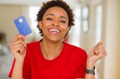 Young african american woman holding credit card screaming proud and celebrating victory and success poster