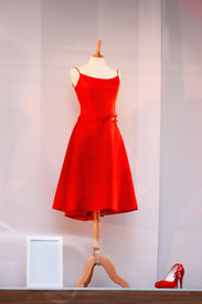 stock photo of dress mannequin  - red dress and red shoes in a shop window - JPG