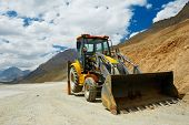 stock photo of wheel loader  - wheel loader excavator machine doing ready to earthmoving roadwork at india mountains - JPG