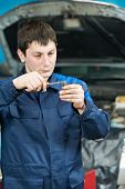 car mechanic inspector checking automobile engine sparking plug with probe at maintenance repair service station
