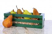 Bartlett and Bosc pears in a wooden crate on a granite counter top. Horizontal format with a white b