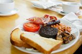 Plate with Full Scottish breakfast containing  toasts, fried eggs, baked beans, grilled black puddin