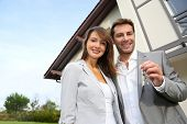 stock photo of 35 to 40 year olds  - Couple in front of new home holding door keys - JPG
