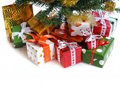 heap of  red  gift boxes  with satin bow  under decorated Christmas tree