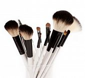 makeup brush set in a glass beaker isolated on white background
