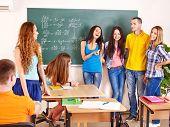 Estudante feliz de grupo em sala de aula perto de quadro-negro.