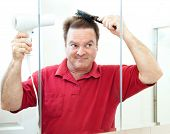 Mature man blow drying his hair in the bathroom mirror.