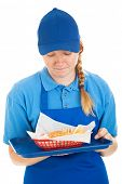 Teenage fast food worker disgusted by the burger and fries she's serving.  Isolated on white.