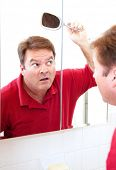 Mature man in his forties uses a mirror to check for bald patches in his hair.