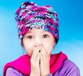 seven year old girl wearing a warm winter hat and feeling cold, against blue studio background