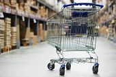 stock photo of trolley  - Shopping trolley cart before Rows of shelves with storage boxes in huge warehouse - JPG