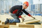 stock photo of membrane  - Roofer builder worker installing roof insulation material - JPG