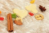 candied fruit, nuts, unbaked biscuits and molds for cookies on a wooden table close-up