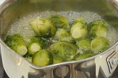 stock photo of cruciferous  - Close up of small cabbages called brussels sprouts boiling in some water in a small stainless steel saucepan on a stove - JPG