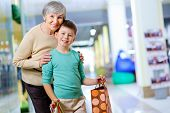 Portrait of happy child holding paperbag with his grandmother near by