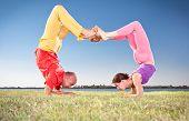 Casal de ioga, homem e mulher fazendo Vrschikasana Escorpião pose na bancada do lago. Conceito de Yoga.